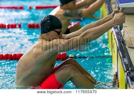 start group young swimmers athletes at a distance in backstroke