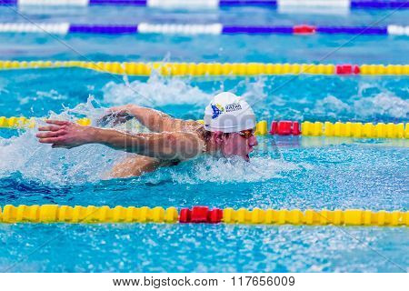young male swimmer athlete swimming butterfly stroke in pool