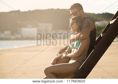 Romantic couple in hug watching sunrise/ sunset together.Young man and woman in love