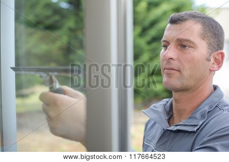 Man wiping window with squeegee
