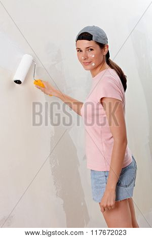 Young Woman Decorate Wall, Paint Droplet In Her Face