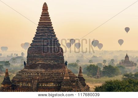 Bagan, Myanmar-december 23 : Unidentified Tourists Stand On Stupa And Admire View Of Balloons Over B
