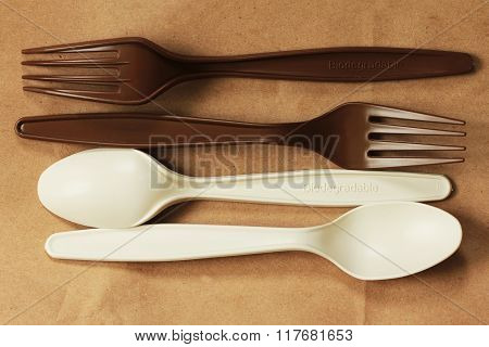 Biodergradable cutlery on brown recycled paper background