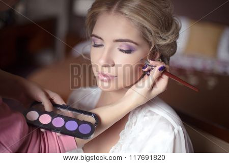 Beautiful Bride Girl With  Wedding Makeup And Hairstyle. Stylist Makes Make-up Bride On Wedding Day.