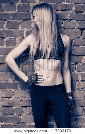 Young blond fitness model in black top and leggins is standing near the red brick wall one hand is on the waist head is turned to the left face is hidden by the hair