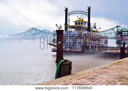 February 1, 2016 in New Orleans, LA:  Historic Creole Queen Riverboat where tourists can travel on the Mississippi River during a dinner cruise with the Crescent City Connection Bridge beyond on the foggy Mississippi River at the Port of New Orleans, LA
