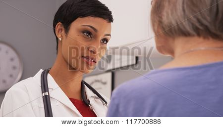 Young Intelligent Female Doctor Talking To Elderly Patient