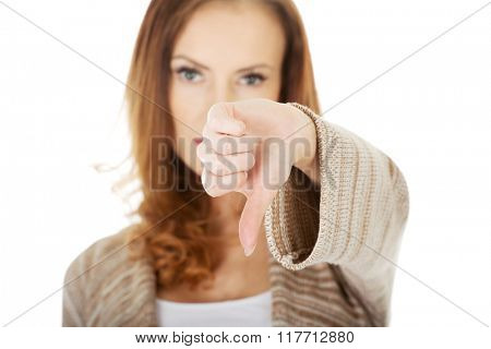 Unhappy woman with thumbs up.