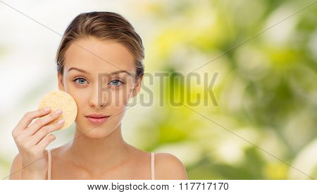 beauty, people and skincare concept - young woman cleaning face with exfoliating sponge over green natural background