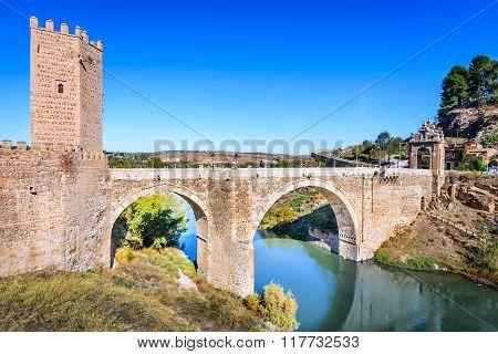 Toledo Spain. Alcantara Bridge ( Puente de Alcantara ) is an arch bridge in Toledo Spain spanning the Tagus River.