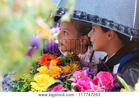 First Grader Girl And Boy Under An Umbrella At  School