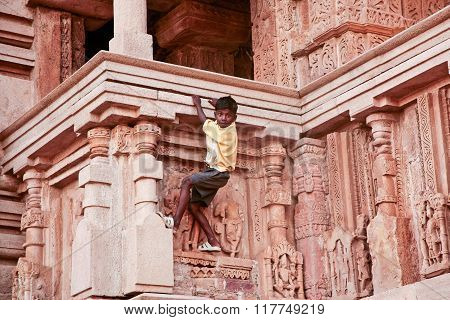 India September 2 2006: the temples in Khajuraho. The boy on the wall of one of the temples of love. On the mural temples of love come to look not only tourists but also curious boys who climb on the walls of temples.