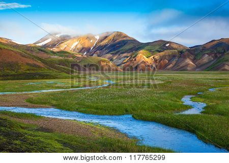 Snow lies in the hollows of colorful rhyolite mountains. Green Valley is flooded with melt water.  Early summer morning in the National Park Landmannalaugar, Iceland poster