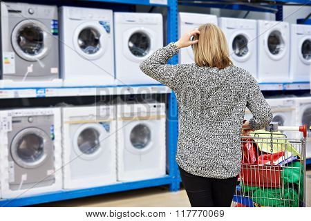Woman Chooses Washing Machine In Shop Of Home Appliances