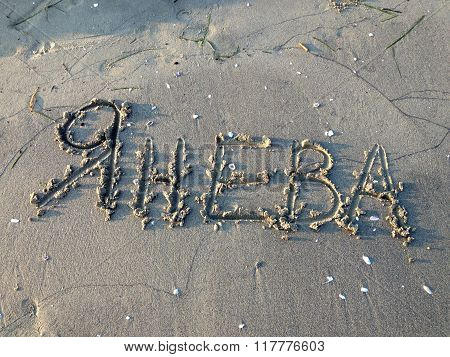 Yaneva female surname written in the sand in Cyrillic