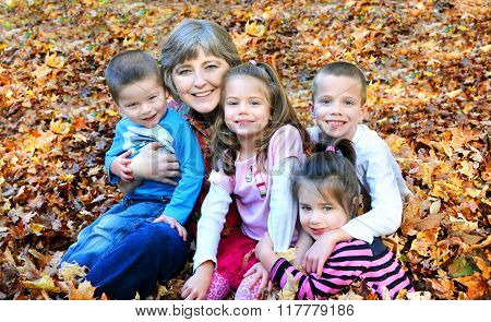 Raking Autumn leaves this grandmother stops to hug up all her grandkids. They are sitting in a pile of leaves and smiling happily. The children include two boys and two girls.