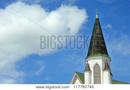 Background image shows steeple of the Church of Christ in Hancock Michigan. Steeple is conical shaped with cross finial. Blue sky surrounds steeple.