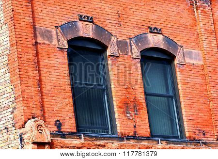 Two windows are topped with red sandstone arches. Building is composed of red sandstone bricks locally mined in the Upper Penninsula of Michigan.