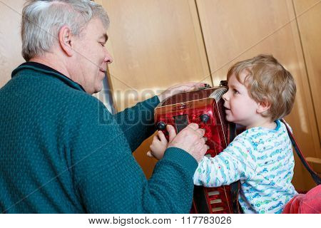 Little kid boy and grandfather playing music instrument