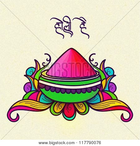 Colour powder in bowl on floral design with Hindi text Holi Hai (Its Holi) for Indian Festival of Colours, Happy Holi celebration.
