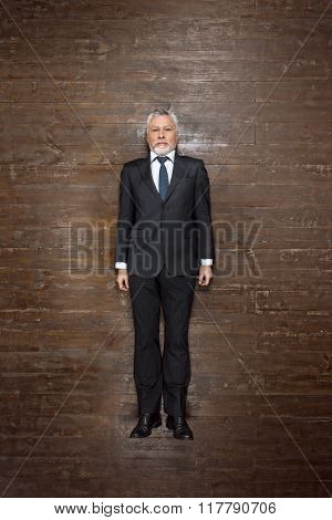 Top view creative photo of senior businessman on vintage brown wooden floor. Businessman looking at camera