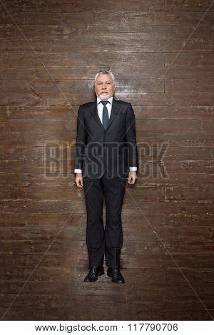 Top view creative photo of senior businessman on vintage brown wooden floor. Businessman looking at camera