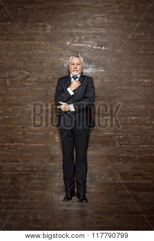 Top view creative photo of senior businessman on vintage brown wooden floor. Businessman looking at camera and straightening tie