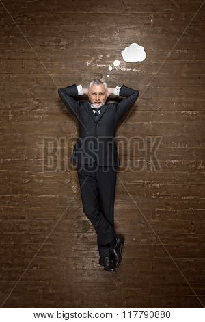 Top view creative photo of senior businessman on vintage brown wooden floor. Businessman lying with blank white cloud near him