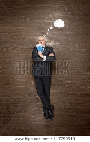 Top view creative photo of senior businessman on vintage brown wooden floor. Businessman lying with blank white cloud near him and holding passport with tickets