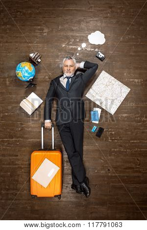Top view creative photo of senior businessman on vintage brown wooden floor. Businessman lying with blank white cloud and holding orange suitcase. There are travel objects near him
