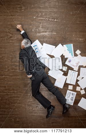 Top view creative photo of senior businessman on vintage brown wooden floor. Businessman flying like superhero with cloak of documents. Businessman is in a hurry