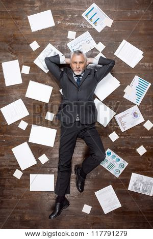 Top view creative photo of senior businessman on vintage brown wooden floor. Businessman lying on office objects and looking at camera. There are documents on floor