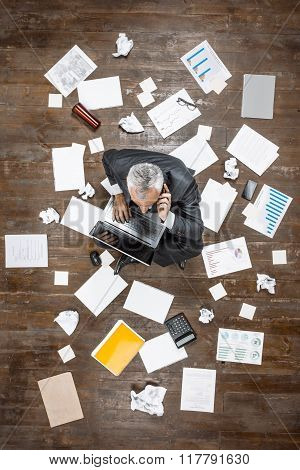 Top view creative photo of senior businessman on vintage brown wooden floor. Businessman sitting on office objects, using mobile phone and working with laptop. There are documents on floor