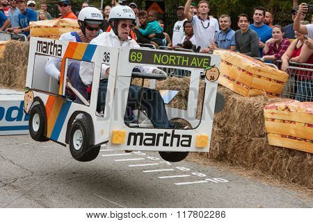 Competitors Racing Bus Vehicle Get Airborne At Soap Box Derby