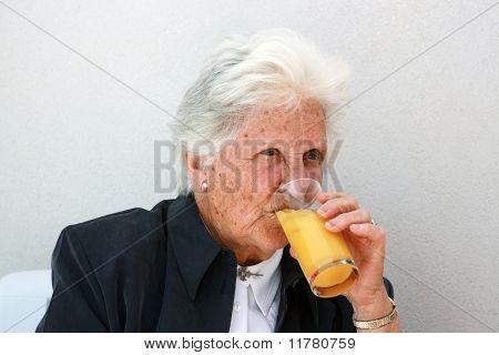 Old Lady Drinking Orange Juice