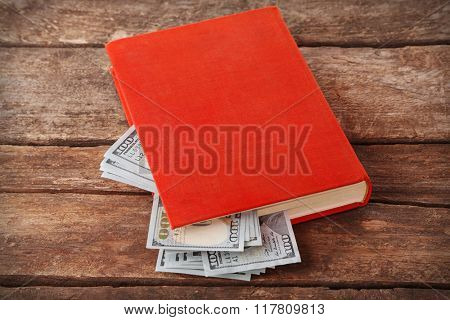 Book with nested dollar banknotes on wooden table. Stash of money