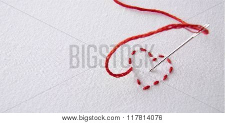 Embroidered Red Heart On A White Cloth With Needle Punctured