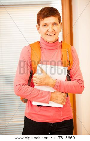 Woman with school bag smiling and holding book like schoolgirl.