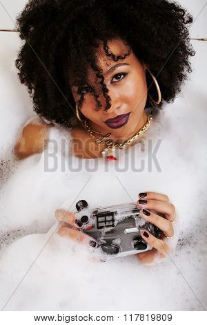 young afro-american teen girl laying in bath with foam, wearing swag jewelry flawless, making selfie