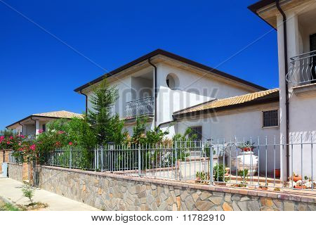 Fence Of White Two-story Cottages With Garden And Balcony