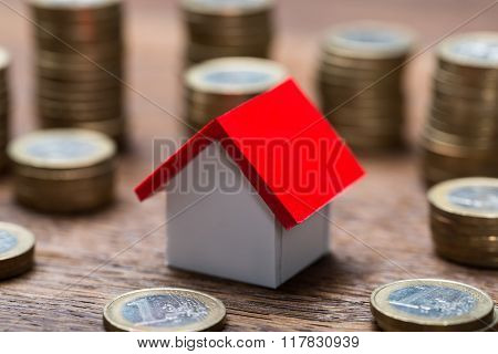 House Model Amidst Coins At Table