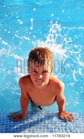 Little Smiling Boy Splash Around In Water In Blue Swimming-pool