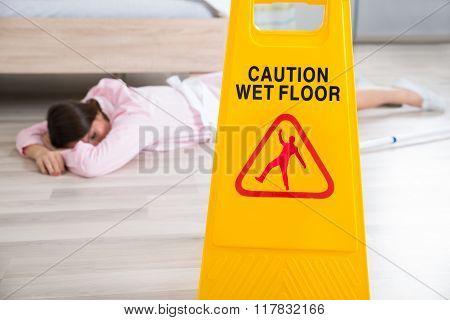 Wet Floor Sign With Fainted Housekeeper Lying On Floor