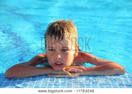 Little Boy Lies In Swimming-pool And Thoughtfully Looks Sideways