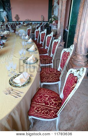Red Chairs And Big Dinner Table With Empty Dishes: Plates With Placemat, Forks, Knives And Goblets