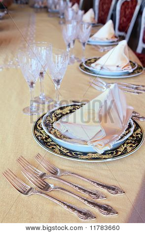 Three Goblets, Four Forks And Two Plates With Placemat At The Dinner Table In Restaurant