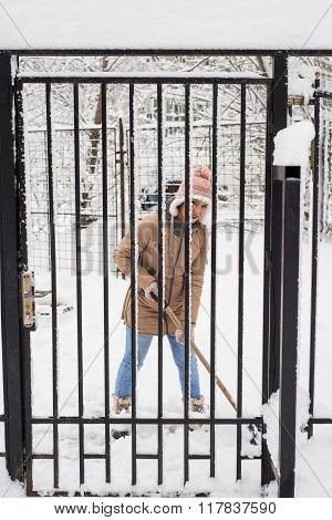 Woman Shoveling Snow By Fence