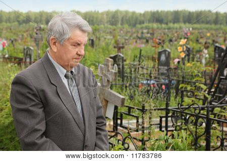 Old Sad Senior In Grey Suit Standing On Cemetery