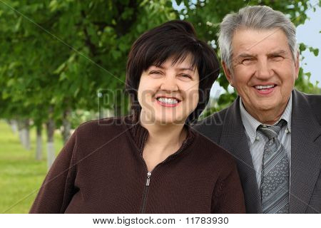 Old Senior And His Adult Daughter Standing And Smiling, Summer Trees