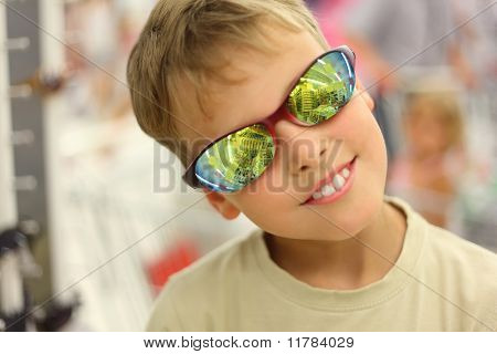 Portrait Of Little Boy Trying Sunglasses With Reflection And Red Rim In Store